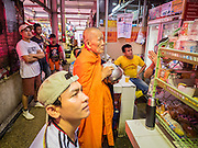"12 JUNE 2015 - BANGKOK, THAILAND: A Buddhist monk on his rounds Khlong Toey Market in Bangkok. The men around the monk were watching the Thai women's football (soccer) team play in the Women's World Cup on television. Khlong Toey (also called Khlong Toei) Market is one of the largest ""wet markets"" in Thailand. The market is located in the midst of one of Bangkok's largest slum areas and close to the city's original deep water port. Thousands of people live in the neighboring slum area. Thousands more shop in the sprawling market for fresh fruits and vegetables as well meat, fish and poultry.          PHOTO BY JACK KURTZ"