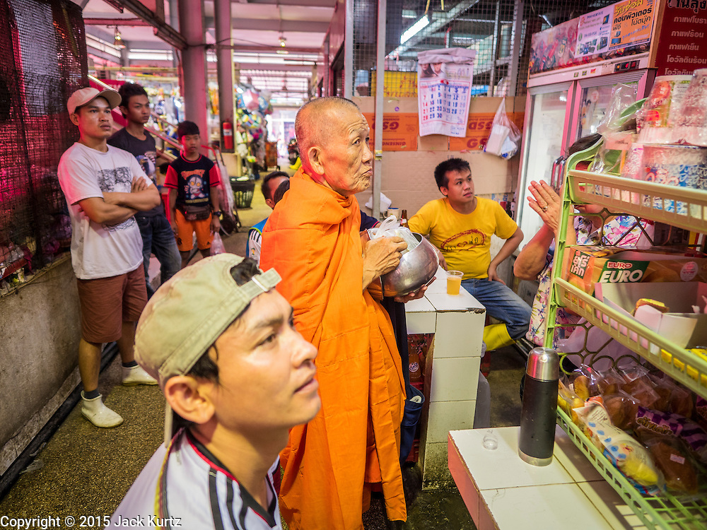 """12 JUNE 2015 - BANGKOK, THAILAND: A Buddhist monk on his rounds Khlong Toey Market in Bangkok. The men around the monk were watching the Thai women's football (soccer) team play in the Women's World Cup on television. Khlong Toey (also called Khlong Toei) Market is one of the largest """"wet markets"""" in Thailand. The market is located in the midst of one of Bangkok's largest slum areas and close to the city's original deep water port. Thousands of people live in the neighboring slum area. Thousands more shop in the sprawling market for fresh fruits and vegetables as well meat, fish and poultry.          PHOTO BY JACK KURTZ"""