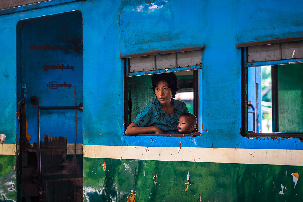 A woman and child peer out of a train waiting for departure at central station, Yangon, Myanmar. 2013