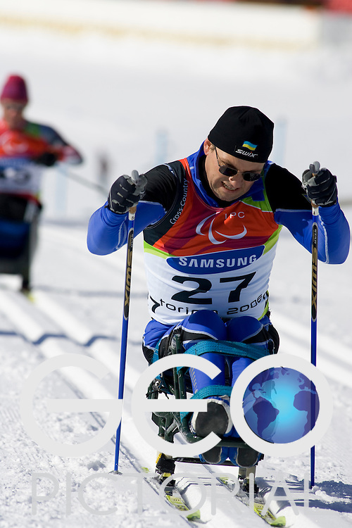 PRAGELATO PLAN, ITALY - MARCH 12: Oleksandr Vasyutynskyy of the Ukraine competes in the Mens Cross Country Skiing 5km Sitting on Day 2 of the 2006 Turin Winter Paralympic Games on March 12, 2006 in Pragelato Plan, Italy.