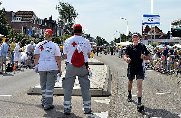Nederland, Nijmegen, 18-7-2014Het vierdaagselegioen loopt over de Via Gladiola Nijmegen binnen. Na een feestelijke intocht volgt de uiteindelijke finish en het ophalen van het kruisje, vierdaagsekruisje, op de Wedren. Vrijwilligers van het nederlandse Rode Kruis staan paraat om hulp te verlenen indien nodig. Een wandelaar uit Israel, met een israelische vlag, vlaggetje, loopt erlangs. Vanwege de vliegramp boven de Oekraine is de intocht sterk versoberd. Geen marsmuziek of muziek van groepen.The International Four Day Marches Nijmegen (or Vierdaagse) is the largest marching event in the world. It is organized every year in Nijmegen mid-July as a means of promoting sport and exercise. Participants walk 30, 40 or 50 kilometers daily, and on completion, receive a royally approved medal, Vierdaagsekruis. The participants are mostly civilians, but there are also a few thousand military participants. In 2004 a restriction on the maximum number of registrations is set to 45,000. More than a hundred countries have been represented in the Marches over the years. Because of the crash of the malaysian airliner, plane over the Ukraine all festivities have been sobered.Foto: Flip Franssen/Hollandse Hoogte