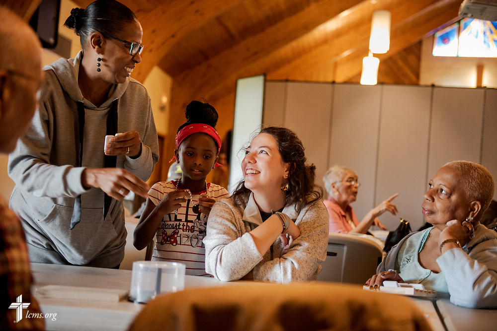 Young Adult Corps participant Madison Ezzell learns a few game tips from Vanessa Seals (standing) as Autumn Berry (behind Seals) and Agnes Joseph look on during time together at the senior community center of Camp Restore on Wednesday, April 4, 2018, in New Orleans. LCMS Communications/Erik M. Lunsford