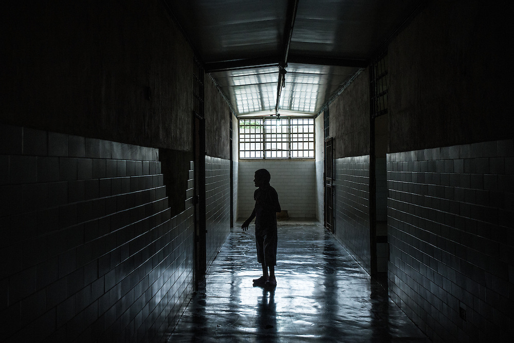 BARQUISIMETO, VENEZUELA - AUGUST 24, 2016: Alba Peralta, a patient diagnosed with epilepsy and mental retardation, and infected with scabies, walks down the hall of the women's ward.  She does not have any of the 5 drugs that doctors prescribed to her for her condition.  The economic crisis that has left Venezuela with little hard currency has also severely affected its public health system, crippling hospitals like El Pampero Psychiatric Hospital by leaving it without the resources it needs to take care of patients living there, the majority of whom have been abandoned by their families and rely completely on the state to meet their basic needs, and who could live much more fulfilling lives if they had the medicines that they need. The hospital has not employed a psychiatrist for over two years. The halls are filled with sounds of patients crying or screaming, and an overpowering stench of urine and feces.  Drugs used to combat bipolar disorder, epilepsy, schizoaffective disorder and chronic anxiety are now in short supply, as are numerous sedatives and tranquilizers needed to care for patients. Members of the nursing staff debate daily which patients are the most unstable, to decide which patients will receive pills and which will go without. When a patient loses control, often the only thing they can do is lock them in an isolation cell to prevent them from hurting themselves, other patients and members of the staff. The hospital does not even have basic hygiene or cleaning supplies.  There is no soap, no shampoo, no tooth paste, no toilet paper.  Patients relieve themselves in the common areas and patio area, and clean themselves only with water. Nearly every patient is infected with scabies because they do not have the resources to bathe properly or to have their threadbare, misfitted clothes washed as often as needed. To make matters worse, the hospital only has running water a few hours a day.  PHOTO: Meridith Kohut for The New York Times