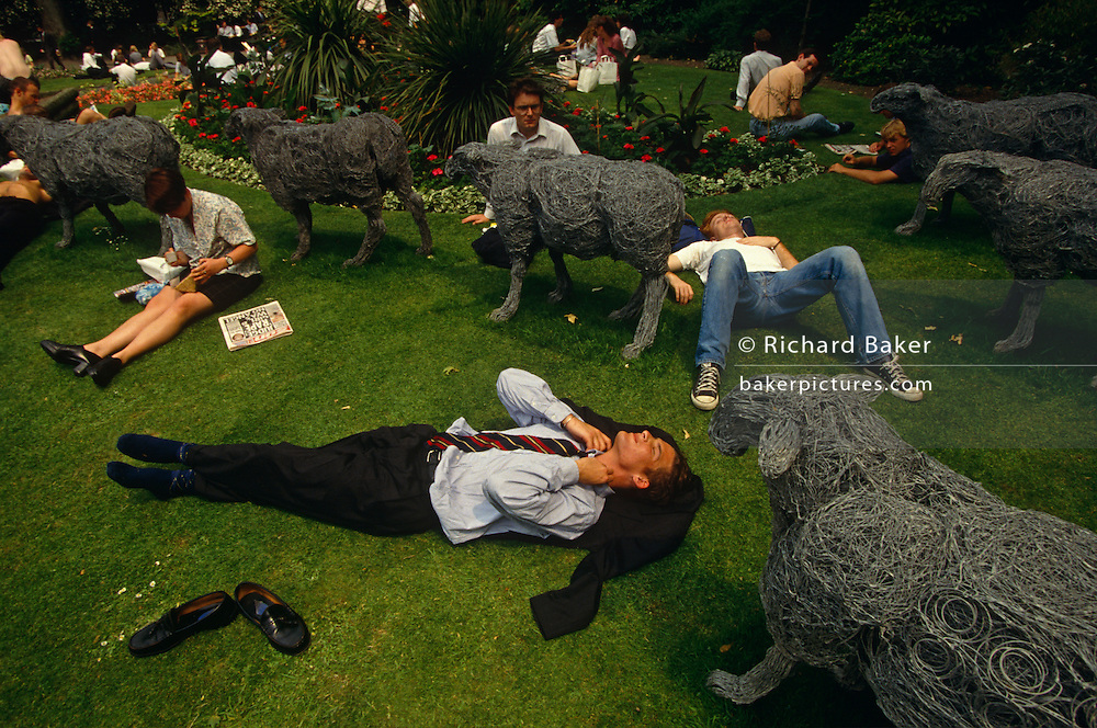 We are looking down from above to office and business workers who are lying down and relaxing in the grass in their lunch break at Finsbury Circus, a circular green park space in the heart of London's financial district, the City of London. Surrounding them is an art instillation of steel sheep that are incongruously grazing among the assorted people, much like they once did when London was a home to livestock en-route to market and other animals used for transport. It is a warm afternoon and in the foreground, a man wearing a dark suit has taken off his polished shoes and is lying his head on his jacket in the warm afternoon, loosening his tight tie and stretching his neck. Elsewhere, a lady is sitting eating a packed lunch with the Sun newspaper and a man a little further behind is in jeans and plimsoll shoes. The City of London has a resident population of under 10,000 but a daily working population of 311,000. The City of London is a geographically-small City within Greater London, England. The City as it is known, is the historic core of London from which, along with Westminster, the modern conurbation grew. The City's boundaries have remained constant since the Middle Ages but  it is now only a tiny part of Greater London. The City of London is a major financial centre, often referred to as just the City or as the Square Mile, as it is approximately one square mile (2.6 km) in area. London Bridge's history stretches back to the first crossing over Roman Londinium, close to this site and subsequent wooden and stone bridges have helped modern London become a financial success.