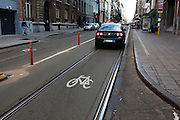 Cycling in Brussels: Tram line, car lane, and bike lane, all combined, resulting in a pretty dangerous mix for cyclists. Photographed on Chaussee de Charleroi, Brussels. In December 2012, a project was proposed with almost 400km of cycling infrastructure for a better connection between Flemish communes and the city of Brussels - one of Europe's most congested and bike-unfriendly cities.