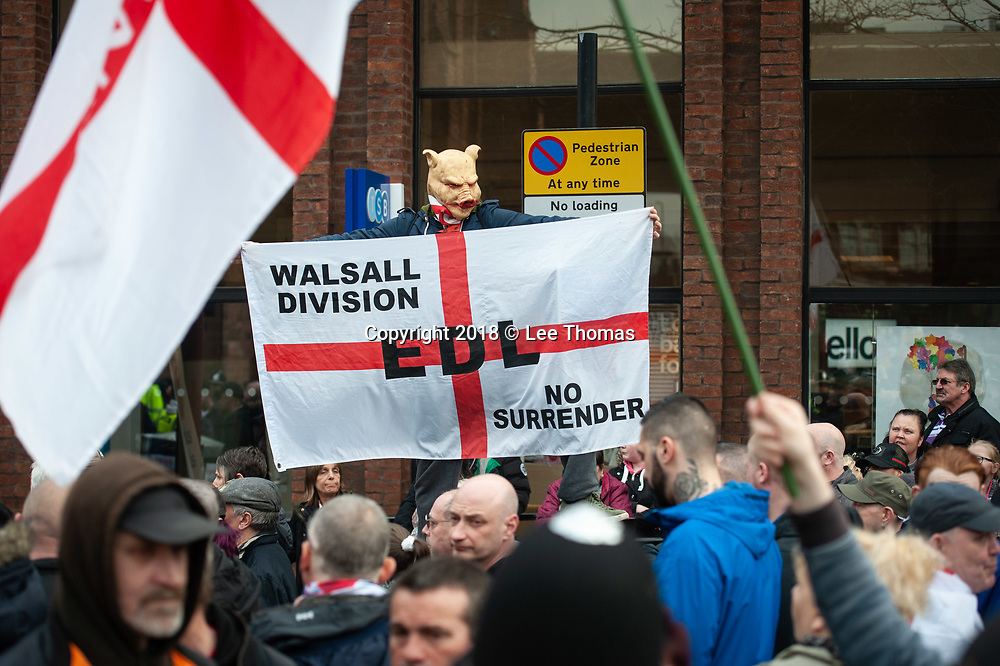 Walsall, West Midlands, UK. 7th April 2018. Pictured: An EDL supporter wears a pig mask at the rally.  / Up to 60 English Defence League supporters take to the streets of Walsall to protest against their claims that the West Midlands town has problems with child exploitation and no-go areas. Scores of police formed a barrier between English Defence League supporters and a vocal anti-fascist contingent, individual protests of which took place only yards away from each other. // Lee Thomas, Tel. 07784142973. Email: leepthomas@gmail.com  www.leept.co.uk (0000635435)
