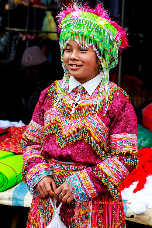 A young lady stands in the colourful traditional clothing and head-dress of the Flower Hmong Tribe, with her purchase, in the morning market in Bac Ha Vietnam.