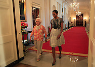 "First Ladies Barbara Bush and Michelle Obama walk into a ceremony  held with Former President George H.W. Bush and President Barack Obama in the East Room of the White House to present the 5,000 ""Daily Point of Life"" on July 15, 2013.  Photograph by Dennis Brack"