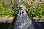 UNITED KINGDOM, London: 09 April 2020 <br /> A couple cross a bridge over Regent's Canal as the sun shines this afternoon. Temperatures for Easter weekend are set to reach 24C degrees, with a reminder to the public to save lives and help the NHS by staying indoors.