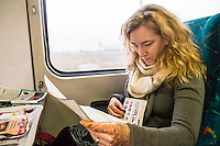A woman on a train between Dehli and Agra India studying travel information and maps.