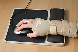 RSI sufferer wearing wrist sports support splint while using computer keyboard