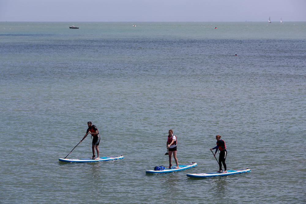 Two women and a man on Stand Up Paddle Boards (SUP) in the English Channel by Folkestone Harbour, Kent, England, United Kingdom. (photo by Andrew Aitchison / In pictures via Getty Images)