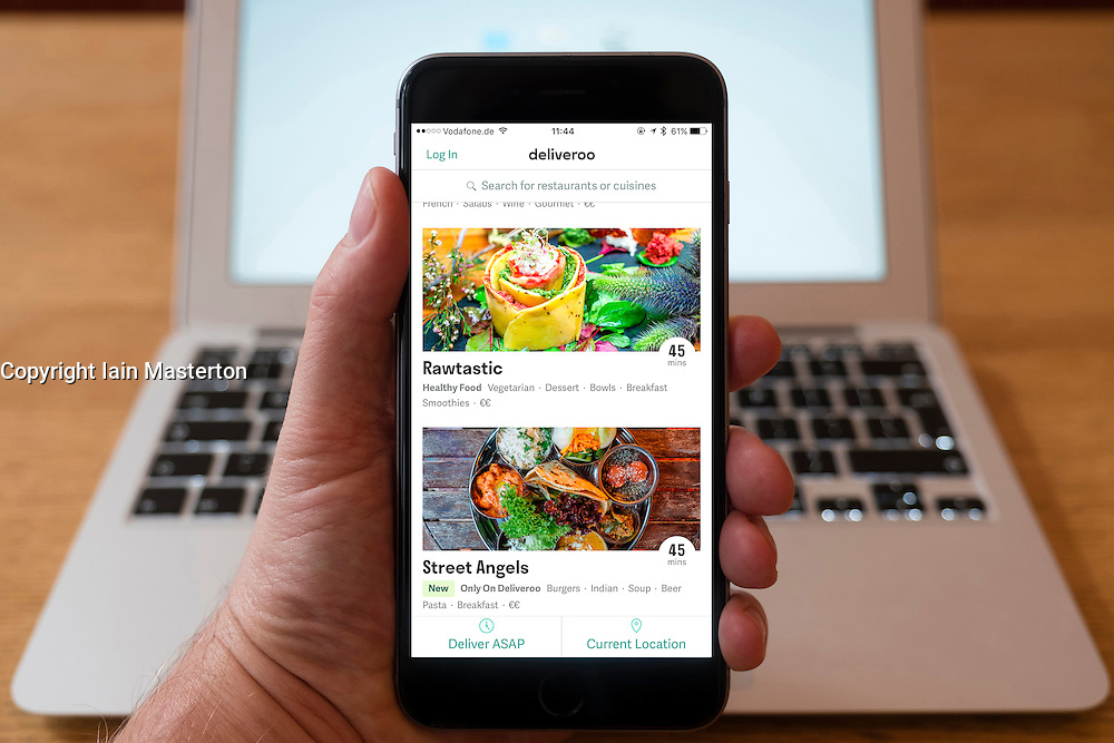 Using iPhone smartphone to display restaurants featured  in  Deliveroo food home delivery service in London,