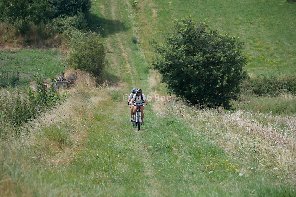 two cyclist pedaling on a grassy countryside road