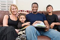 Portrait of happy family sitting on sofa