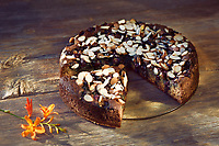 Healthy home-made Banana bread, sugar-free with almond flour, berries and almonds on a table, artistic country style food still life on rustic wooden background