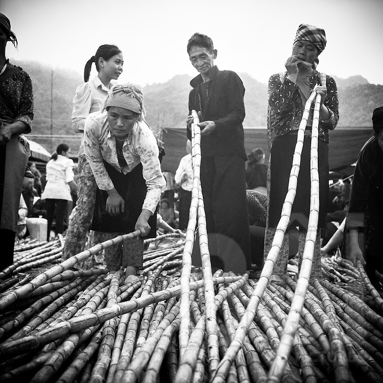 Ethnic minority men and women inspect sugarcane on a small rural market in Ha Giang Province, Vietnam, Southeast Asia