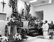 Father kneels with baby before the Christmas altar in an Hispanic Catholic church in Charlotte, NC>