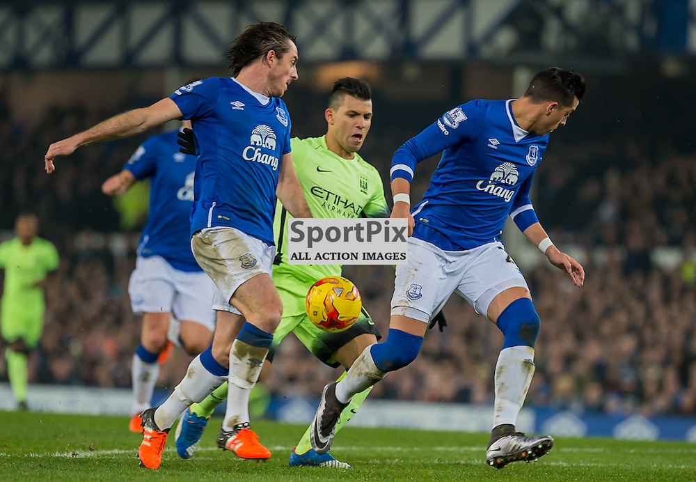 Manchester City forward Sergio Aguero closely marked by Everton defender Leighton Baines and Everton defender Ramiro Funes Mori in the Football League cup semi-final first leg at Goodison Park, Liverpool
