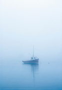 Lobster boat moored in a misty harbor, Osterville, Cape Cod, Massachusetts, USA.