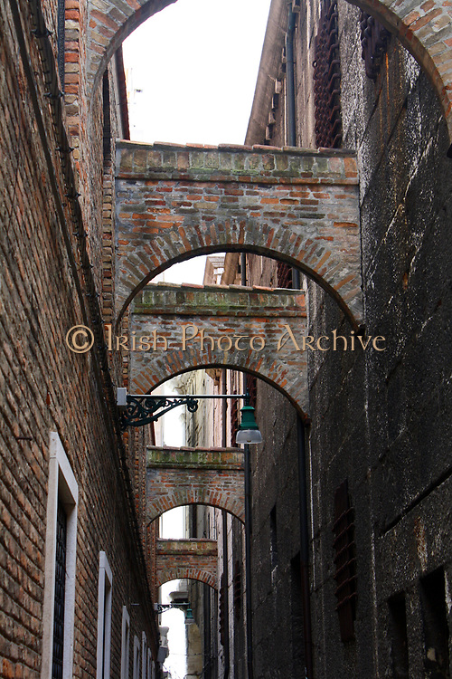 Stone Arches between buildings along canal in Venice 2013.