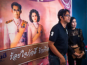 """14 FEBRUARY 2017 - BANGKOK, THAILAND: A newly married couple poses for a photo in front of Bhumibol Adulyadej, the Late King of Thailand, and his wife, Queen Sirikit in the Bang Rak district in Bangkok. Bang Rak is a popular neighborhood for weddings in Bangkok because it translates as """"Village of Love."""" (Bang translates as village, Rak translates as love.) Hundreds of couples get married in the district on Valentine's Day, which, despite its Catholic origins, is widely celebrated in Thailand.      PHOTO BY JACK KURTZ"""