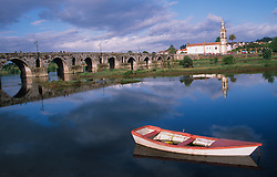 Europe, Portugal, Minho region, Ponte de Lima, rowboat in river by historic bridge and church