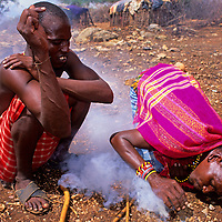 Africa, Kenya. Two Maasai males demonstrate fire starting
