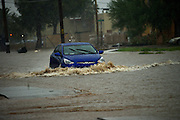 An passenger vehicle drives through flooded streets during a monsoon storm, Sonoran Desert, Tucson, Arizona, USA.