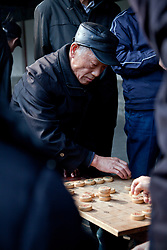 "Man making a move in the Chinese chess game of Xianggi (pronounced ""shyahng chi"") in park arcade approaching the Temple of Heaven, Beijing."