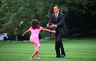 President Barack Obama gets a warm welcome home from daughters Sasha and Malia and first dog Bo on the South lawn of the White House on September 15, 2009.   photo by Dennis Brack