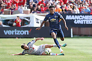 Liverpool midfielder Adam Lallana (20) tackles Manchester United Defender Demi Mitchell during the Manchester United and Liverpool International Champions Cup match at the Michigan Stadium, Ann Arbor, United States on 28 July 2018.