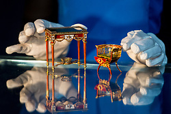 "© Licensed to London News Pictures. 31/05/2019. LONDON, UK. A staff member presents ""A fine and rare Fabergé gold and enamel miniature bonbonnière chair"" by workmaster Michael Perchin, circa 1900, and ""A fine and rare Fabergé vari-colored gold, guilloché enamel and nephrite miniature table bonbonnière"" by workmaster Michael Perchin, 1899-1908, (Est: £800,000 – 1.2 million) at a preview of works from the upcoming sale of Russian Pictures, Works of Art, Fabergé & Icons Sales at Sotheby's, New Bond Street, on 4 June 2019.  Photo credit: Stephen Chung/LNP"