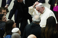 Jan 07th 2015 Vatican City, Pope Francis attends his weekly general audience. The pope changes his biretta with a child