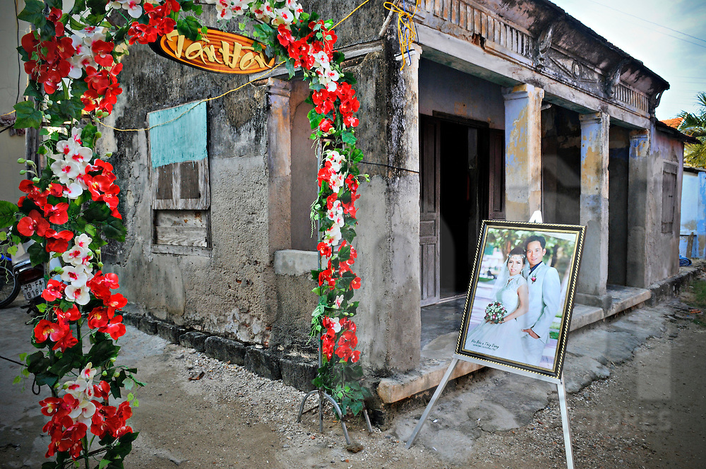 A wedding couple's picture is placed at the entry of a flowery gate. Khanh Hoa province, Vietnam, Asia