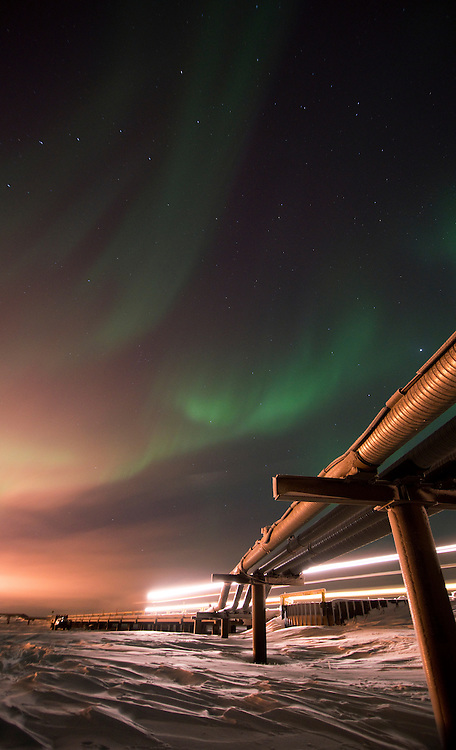 A water truck drives across the CD-2 pipe bridge as the aurora borealis falls over Alpine Oilfield on Alaska's north slope.