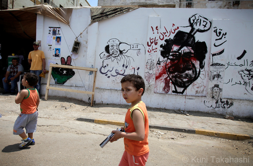 A boy holding a toy gun walks in front of the wall with graffiti of anti- Col. Muammar Qaddafi  in Benghazi, Libya on May 26, 2011. .Photo by Kuni Takahashi.