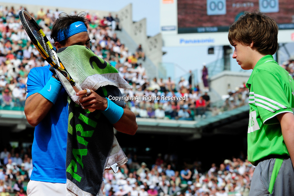 24.05.2011 French Open Tennis from Roland Garros Paris. Rafael Nadal of Spain wipes his face while a ball boy looks on on day three of the French Open tennis championships.