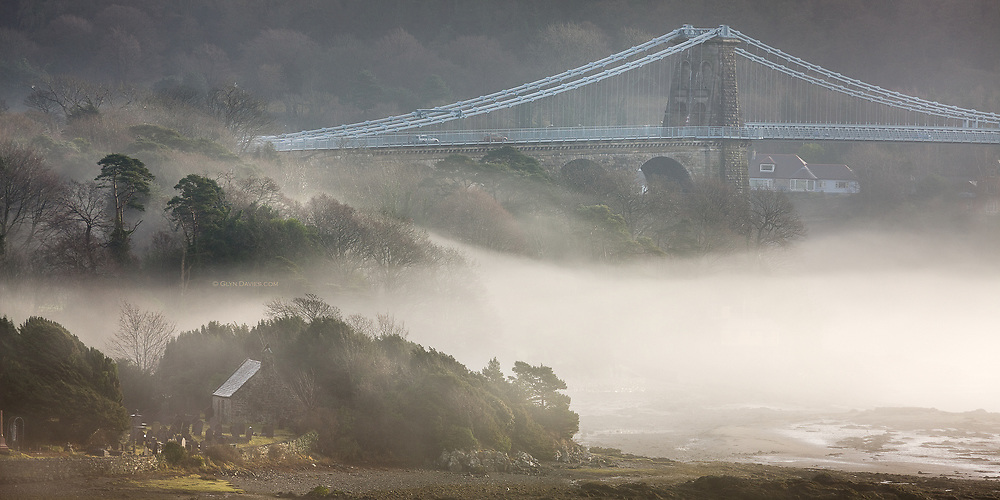 """An eary morning fog rolls in off the sea, shrouding the idyllic church and graveyard of Ynys St Tysilio, Anglesey.<br />