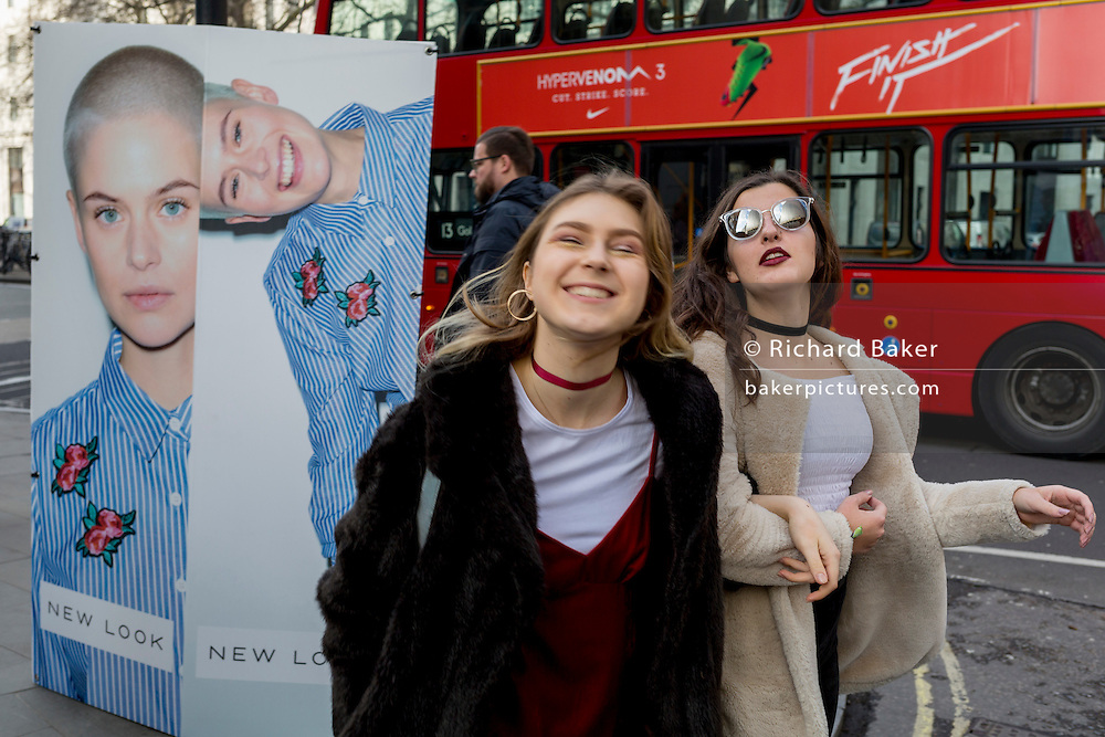 "Models have fun next to a street billboard for high-street retailer New Look, outisde London Fashion Week in the Strand, on 17th Febriary 2017, in London, England, United Kingdom. London Fashion Week is a clothing trade show held in London twice each year, in February and September. It is one of the ""Big Four"" fashion weeks, along with the New York, Milan and Paris. The fashion sector plays a significant role in the UK economy with London Fashion Week alone estimated to rake in £269 million each season. The six-day industry event allows designers to show their collections to buyers, journalists and celebrities and also maintains the city's status as a top fashion capital. (Photo by Richard Baker / In Pictures via Getty Images)"
