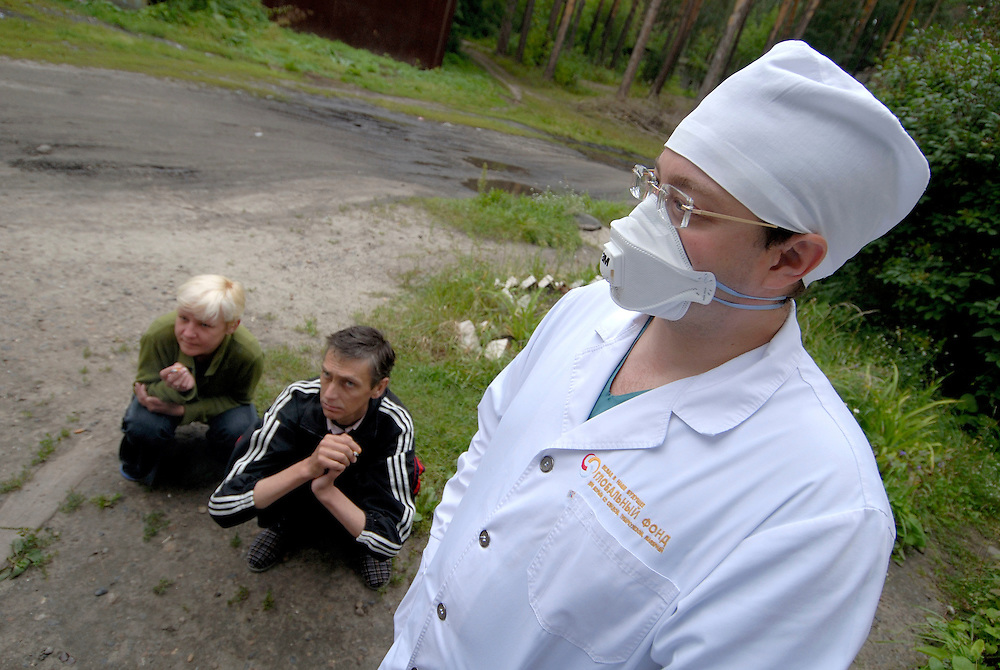 Russia. Tomsk (Siberia). 24.08.2007. TB Hospital. MDR (Multi Drug Resistant) ward. Dr. Dimitri Shegertsov, Deputy Head of MDR Division, outside with two patients smoking in the background.