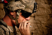 Specialist Brandon Kelley takes a drag from a cigarette after a firefight with the Taliban at Combat Outpost Nolen.