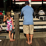 Caroline Smith, 11, left, Avery Smith, 6, center, and their father Dennis Smith watch church service at The Anchor Sunday June 1, 2014 on the Wilmington, N.C. waterfront. The family had stopped while on their morning walk to listen to the sermon. (Jason A. Frizzelle)