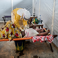 19/04/2014. Quartier de Kango II. Gueckedou. Guin&eacute;e Conakry.  <br /> <br /> Suite &agrave; un appel, une &eacute;quipe de MSF va chez Finda Marie Kamano, 33 ans, elle ressent une grande faiblesse, avec des vomissements et dysenterie. Avec la fi&egrave;vre, et les saignements de nez, ce sont les sympt&ocirc;mes provoqu&eacute;s par le virus Ebola.<br /> <br /> En protection totale, un m&eacute;decin ausculte Finda, elle se plaint de fortes douleurs au ventre.<br /> <br /> Following a call, an MSF team goes to consult Finda Marie Kamano, 33 years, she feels great weakness with vomiting and dysentery. With fever, and nose bleeds, what the symptoms are caused by the Ebola virus.<br /> <br /> Total protection, medical auscultates Finda, she complained of severe stomach pains.<br /> <br /> &copy;Sylvain Cherkaoui/Cosmos/MSF