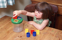 Young girl sitting at table playing with shapes,