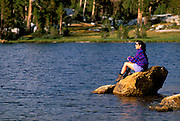 Woman sitting on a rock along the shore of Boothe Lake in the Cathedral Range, Sierra Nevada Mountains, Yosemite National Park, California.