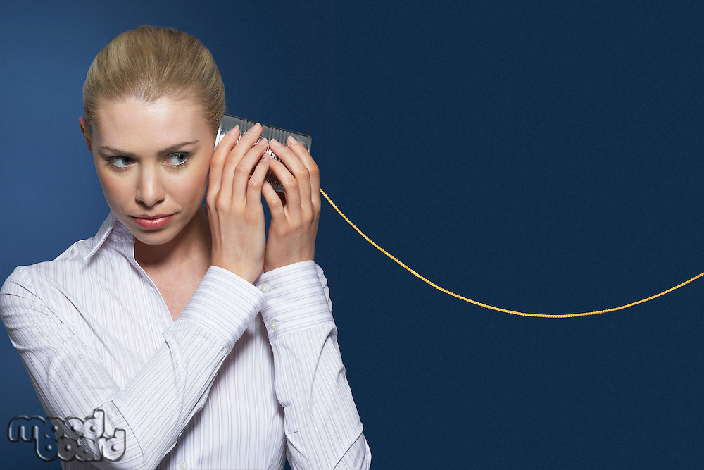 Woman listening to tin can phone against dark background