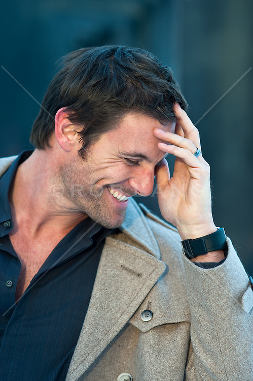 Man laughing with his hand to his forehead
