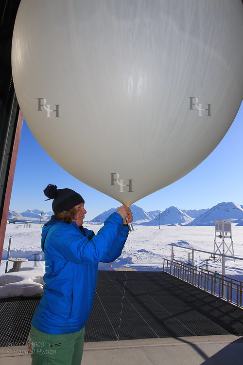 Woman prepares to launch weather balloon at the international science village of Ny-Alesund on Spitsbergen island in Kongsfjorden; Svalbard, Norway.