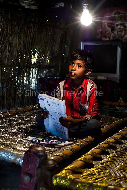 4th April 2014, Shakarpur, New Delhi, India. Deepak (7) does homework under a light bulb in his home on the Yamuna Bank,  Shakarpur, New Delhi, India on the 4th April 2014<br /> <br /> Deepak goes to makeshift school under a metro bridge, near the Yamuna Bank Metro station in Shakarpur<br /> <br /> Rajesh Kumar Sharma (born 01/02/1970), started this makeshift school in 2011. Six mornings a week he teaches underprivileged children for three hours while his younger brother replaces him at his general store in Shakarpur. His students are children of labourers, rickshaw-pullers and farm workers. This is the 3rd site he has used to teach under privileged children in the city, he began in 1997. <br /> <br /> PHOTOGRAPH BY AND COPYRIGHT OF SIMON DE TREY-WHITE<br /> + 91 98103 99809<br /> email: simon@simondetreywhite.com<br /> photographer in delhi<br /> journalist